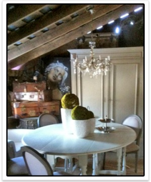 White round table with large armoire and greenery