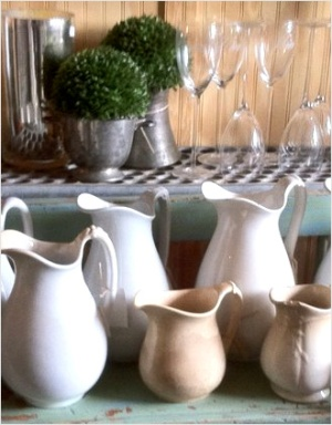 White and cream pitchers with greenery