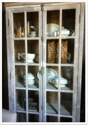 Large battered armoire with white dishes