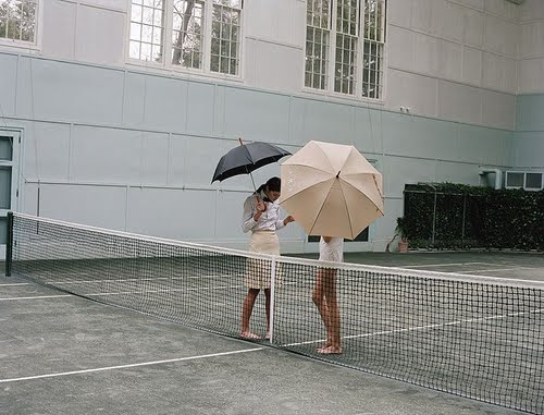 2 girls in pencil skirts with umbrellas on a tennis court