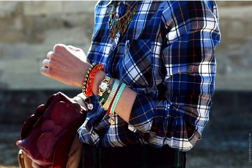 Blue plaid shirt with stacks of colorful of bracelets