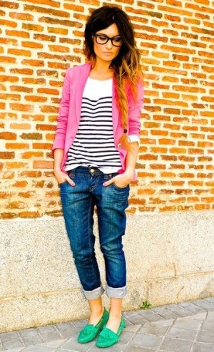 A girl with stripes, pink cardigan, blue jeans and kelly green shoes