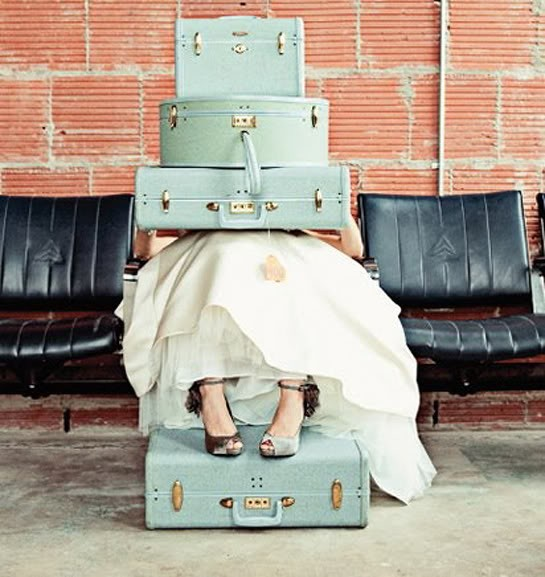 Light blue vintage luggage, old airline seats and gown