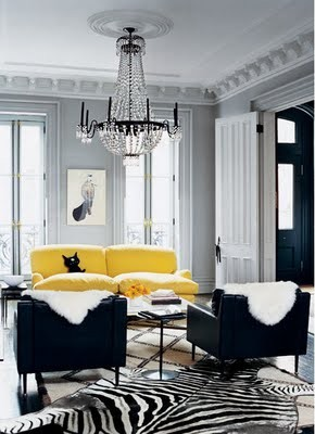 jenna lyons yellow sofa,black chairs, crystal chandelier and zebra rug via domino