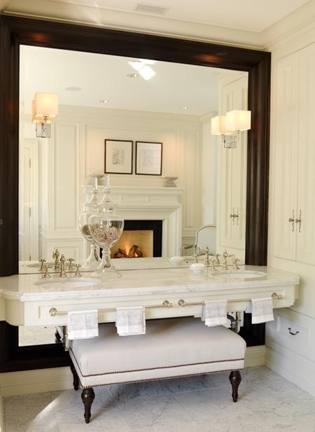 Bath with large dark mirror and ottoman