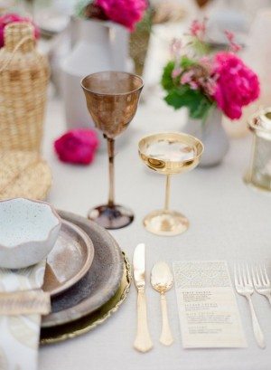 table setting with pink glowers and gold flatware