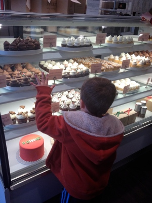 Little boy window shopping for cupcakes